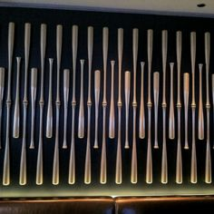 Gold baseball bats installed on the wall at a sports bar. Cool decor for a man cave.