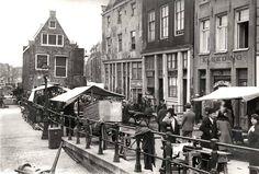 1935. Sunday market at the Joden Houttuinen (Jodenhoek) in Amsterdam. In the background the Goslerhuis next to the Sint Antoniesluis. The Jodenhoek was prior to the German occupation a neighborhood where many Jews lived. It was comprised of the Jodenbreestraat, Uilenburg, Vlooienburg, Waterlooplein, Rapenburg and the Nieuwe Herengracht, later also the Nieuwmarkt, Sint Antoniesbreestraat, the Plantage, Weesperstraat and Weesperplein up to the Nieuwe Kerkstraat. #amsterdam #1935…