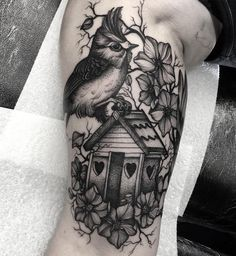 A cute and pretty sleeve tattoo. The grayscale tattoo suits the design perfectly. You can see a bird perched on a birdhouse that looks to be up in a tree filled with flowers. Everything adorable combined in just one design.