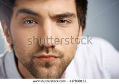 Close up portrait of serious elegant handsome young businessman in white shirt looking at camera raising one eyebrow. Studio, isolated on grey background.