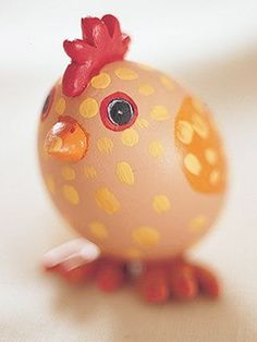 This egg chicken's beak, comb and feet are made from clay; wings and eyes are hand-painted on a brown shell