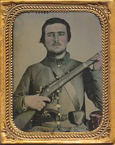 this son of the south wears the distinct uniform of the 1st Regiment South Carolina Orr's Rifles which was a grey frock with collar, cuff's and facing's trimmed green and in fact the button just next to his trigger guard is in fact a South Carolina Palmetto. Accouterments are very plain with a cartridge box strap worn across the breast and a small leather belt which is worn on the outside of the coat.