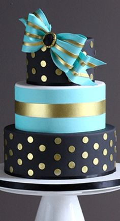 Black and gold polka dots with blue centre tier and gold ribbon