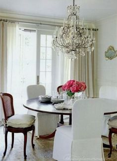 Beautiful dining room. Love the chandelier & linen covered chairs. Dreamy!