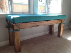 A farmhouse bench cushion with ties to keep it in place. There is a rug mat underneath that also helps so it won't shift.