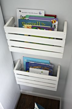 Find a wooden crate at a craft store, paint any color you want, cut in half with table saw, attach hanging brackets with screws and attach to wall.  Great idea!
