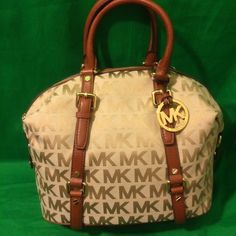 """Michael Kors Beige Ebony Signature Medium Bedford Michael Kors Beige Ebony Signature Medium MK Bedford Leather Satchel Bowling Bag.  Monogram block print jacquard with white leather trim and golden hardware Lined interior with zippered pocket and 4 open slip pockets Zippered top closure with a removable Kors circular logo hang charm Dual buckled top leather handles have a drop of about 5"""" or use removable and adjustable shoulder strap. Measures approximately 12""""-18"""" (L) x 11"""" (H) x 5"""" (W)…"""