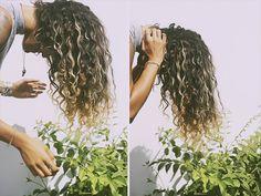chica agacha su cabeza y seca sus rizos al natural