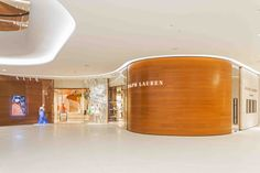 Taking inspiration from the forms of Richard Serra, the interior storefront is comprised of full height curving teak wood and glass panels that mimic the curvilinear character of the mall, so that the spaces flow seamlessly from one to the next.