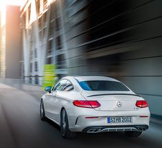 Rear view of a white Mercedes-AMG C 43 4MATIC Coupé on the road.