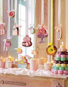 Des suspensions en carton, avec pâtisseries peintes en couleurs à accrocher avec des rubans pastels