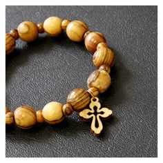 Olive wood's rich grain makes this simple bracelet a treasure. The wooden beads are strung on a black elastic cord and a small cross completes the design. It is constructed of smooth rich wood that just looks better the more it is worn.