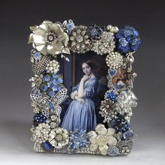 An elegant frame composed of over thirty pieces of vintage costume jewelry in cool shades of sapphire blue with silver, irridescent crystal, rhinestones and pearls. There is a unique blue rose, silver and crystal butterfly, a lovely painted cameo, English china flowers and a silver