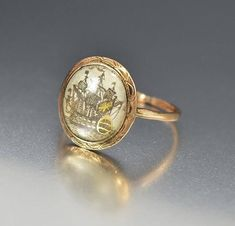 Splendid antique English Georgian ring dating to the late 18th Century, featuring a frigate ship sepia on thin wafer accented with gold highlights outlining the