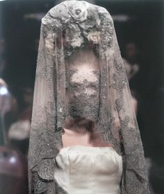 """Alexander McQueen S/S 2007  """"Though she is clad in white with clear bridal suggestions, the antique quality of her veil, the ashen color of which seems to coat the lace like a film of dust accumulated over years of neglect, suggests a general sentiment of something sinister lurking beneath the bridal veil."""" taken from Alexander McQueen: Genius Of A Generation"""