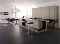 Leicht German Kitchens.  Style FRAME-H in textured oak slate wood veneer with stainless steel coloured metal profile to visibly frame the veneered panels.  With coordinating silk matte black lacquer shelf elements.