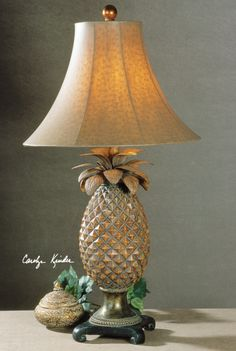 This timeless pineapple motif is presented in hand rubbed brown glaze with atlantis bronze accents. The round bell shade is finished in a brown ostrich texture. #lamps #pineapples @Uttermost