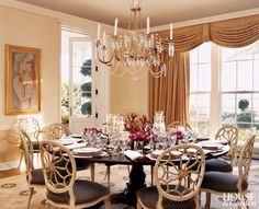 A custom dhurrie rug in a sea inspired pattern in pale gold and brown complements the dining chairs and warm gold drapes and pale gold walls in the Bunny Williams designed dining room in the home of Wilbur and Hilary Geary Ross.