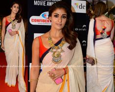 Nayanthara attended day two of SIIMA Awards wearing a simple off-white khadi saree teamed with contrast red sleeveless blouse. Side swept hair and a statement necklace by Amrapali Jewels completed her red carpet look. She looked simple and elegant. Indian Attire, Indian Ethnic Wear, Indian Outfits, Indian Style, Kerala Saree Blouse Designs, Off White Saree, Khadi Saree, Sari Design, Modern Saree