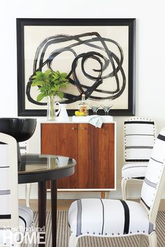 In a corner of the great room, punches of black and white prove that opposites do, indeed, attract. The minimalist bar cabinet, black lacquered game table, and bold, graphic art fit the homeowners' request that designer John Stefanon keep things simple, but statement-making.
