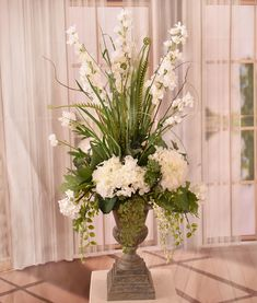 "A light and airy mix of beautiful white delphinium and hydrangea with cascading vines for extra interest and texture. Accented with green grasses for added dimension. Created in a gorgeous tall resin urn. Measures 29"" H x 13"" Wx10"" D"