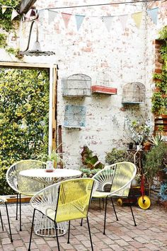 Retro-inspired outdoor furniture, a touch of colour and a potted plants turn this small sunny courtyard into a functional space. Photo: Derek Swalwell | Styling: Heather Nette King,