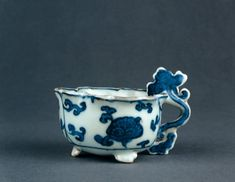 Porcelain cup with a lobed mouth rim, three small feet and a handle of lingzhi shape. Decorated in underglaze blue. Floral scroll on the outside and a lingzhi shaped flower head in the centre inside. Ming dynasty Wanli period.