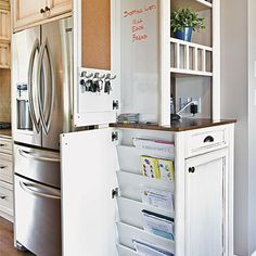 """Kitchen organizer cabinet has a 3⁄4"""" butcher-block counter for the phone. Above the counter are mail slots and open shelving. Below, a junk drawer & cabinet has a pullout charger drawer. A 3-1⁄2-in. deep recess contains a whiteboard w/ marker storage, a corkboard, & key hooks. In the lower unit, there is a similar recess fitted with slots for the children's important school papers.  The cabinet faces a small seating area and is ideally located close to the rear entry and mudroom."""