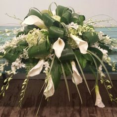 White calla lily and tea leaf casket spray