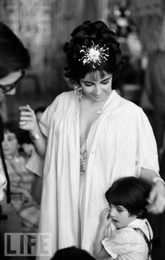 During a break in the filming of Cleopatra, Elizabeth Taylor ruffles the hair of Liza Todd, her daughter with her third husband, the late Mike Todd. At the time, Taylor was married to Eddie Fisher, but had begun a tempestuous affair with her Cleopatra costar Richard Burton