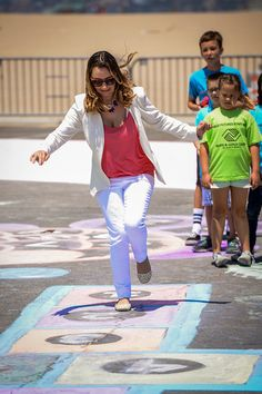 Actress Beverley Mitchell trys her hand a hop scotch on a 40,000 square chalk mural near the Santa Monica Pier. The chalk art was created to promote outdoor activities for kids during the summer.  RoseArt has donated $50,000.00 to the Boys and Girls clubs for summer activities.   ( Photo by David Crane/Los Angeles Daily News )