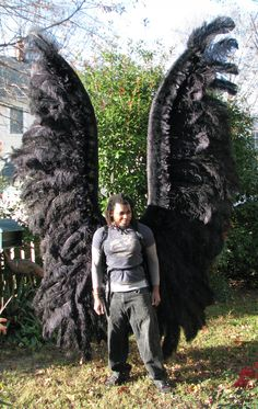 Black archangel costume wings, front view, modeled by Fedner Jeneste