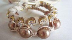 O conjunto contém:  -1 pulseira Shambala regulável, feita com cordão encerado na cor bege e pérolas douradas  -1 pulseira regulável de couro na cor bege com strass grande dourado R$40,00