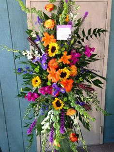 Colorful standing funeral Spray with sunflowers, orange roses and lilies with purple garden accents and white dendrobium orchids Casket Flowers, Grave Flowers, Cemetery Flowers, Funeral Flowers, Wedding Flowers, Arrangements Funéraires, Funeral Floral Arrangements, Large Flower Arrangements, Artificial Floral Arrangements