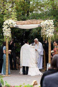 Gold post chuppah with branches and hanging flowers.