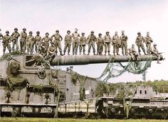 US soldiers of the 10th Armoured and 45th Division, 7th US Army stand on the cannon of a captured German Rail Gun in Rentwertshausen, Germany. April 1945.  The 274mm. Kanone (Eisenbahn) 592(f) was originally a French Schneider Modèle 1917 ALVF weapon captured by the Germans in 1940. It could fire a 237.5 kilogram projectile to a maximum range of 29,100 meters.
