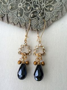 "Fabulous earrings featuring rhinestone ""crowns"" with faceted deep blue glass teardrop beads.  Tilliegirlstudio"