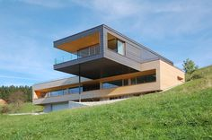 A home sits in Austria on a sloped green meadow with a cantilevered top floor clad in copper that features an overhang for sun protection in the summer.