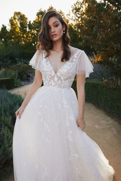 Leafy lace appliqués on a V neck illusion bodice with flutter sleeves. Full A-line skirt scattered with appliqués throughout. Lis Simon Wedding Dresses, Dream Wedding Dresses, Bridal Dresses, Bridesmaid Dresses, Gown Wedding, Wedding Cakes, Wedding Rings, Garden Wedding Dresses, Civil Wedding Dresses