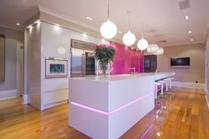 Kitchen with pink wall paper and lighting accents