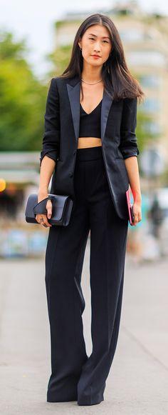 Un pantalon smoking très long et large, une grande veste smoking décolleté et un crop top. Le tout en noir avec une pochette.