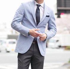 Light blue jacket / grey trousers / white shirt / blue tie with white dots.