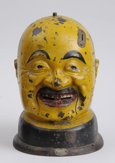 AMERICAN PAINTED CAST-IRON CANDY DISPENSER, EARLY 20TH C.   In the form of the head of a laughing man, with coin slot and openings in mouth to dispense contents, bearing label with patent date of August 26, 1902. Provenance: Property from the Collection of Gerald Kornblau. 14 x 9 3/4 x 10 1/4 in.