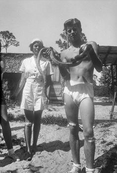 Young John Kennedy in his undies, covered in plasters, holding a snake