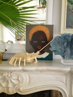 Local art, palms, and ocean beauties on India's fireplace mantel. @HSN