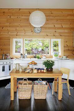 U-mallinen keittiö katsoo sisääntulon puolelle ylärinteeseen, joka on istutettu täyteen perennoja, Ikean kalusteet ja tasot ovat kepeät mustan sokkelin päällä.