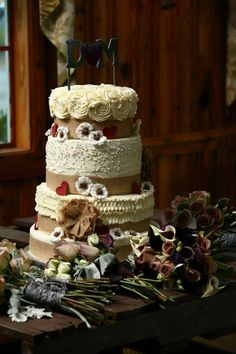 4 tier country style wedding cake with burlap ribbon and flowers.