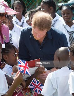 Akia Slocombe shows Prince Harry a picture of her father Tim who was injured while serving in Afghanistan during his visit to a community sports event on the ninth day of an official visit to the Caribbean on November 28, 2016 in St Geoorges, Grenada. Prince Harry's visit to The Caribbean marks the 35th Anniversary of Independence in Antigua and Barbuda and the 50th Anniversary of Independence in Barbados and Guyana.