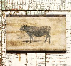 """Fleming Cow Scroll 18.00 Our Fleming Cow Scroll is made on artisan paper and is weighted at the top and bottom with metal.  The perfect accompaniment to any country farmhouse kitchen.  18"""" w x 11"""" H"""