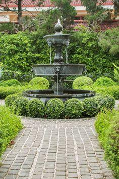 Nature background. Fountain in english garden design.